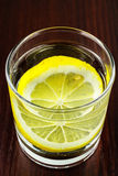 Glass of transparent purified water with slice of lemon, on wooden table Royalty Free Stock Image