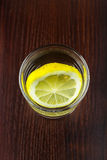 Glass of transparent purified water with slice of lemon, on wooden table, top view Royalty Free Stock Photo
