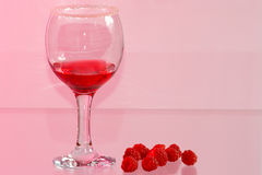 Glass of transparent red liquor and raspberry. The glass of transparent red liquor and raspberry on a pink background Stock Photo