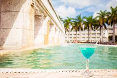 Glass of tropical cocktail on a background of swimming pool Royalty Free Stock Photos