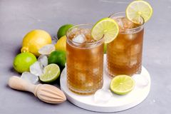 Glass of Tsasty Ice Tea with Ice Cubes and Citrus Cold Summ er Beverage Wooden Squeezer and Raw Lemons and Limes on Background. Glass of Tsasty Ice Tea with Ice Royalty Free Stock Image
