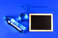 Glass, tube, closed bottle of water and chalkboard for text Stock Image