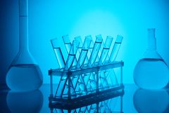Glass tubes with liquid on stand and glass flasks on table. On blue stock images