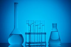 Glass tubes on stand and glass flasks with liquid on table. On blue royalty free stock images