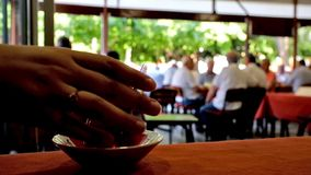 Glass of turkish tea. Drink a glass of hot Turkish tea in crowded cafe with seniors, playing popular local tiled-based game, named Okey (rummikub), Antalya stock video