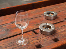 A glass and two ashtrays outside a pub. An empty glass and two full ashtrays on a table outside a pub in Trieste Stock Photo