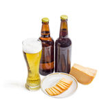 Glass and two bottles of beer, cheese on light background Royalty Free Stock Images