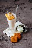 Glass of vanilla milkshake with whipped cream royalty free stock image