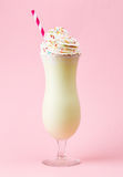Glass of vanilla milkshake with whipped cream on pink background Royalty Free Stock Images