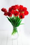 Glass vas med röda tulpan på den wood tabellen Royaltyfri Foto