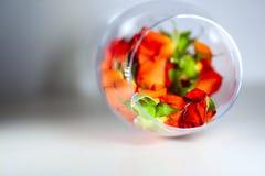 Glass vas som fylls med röda roskronblad aromatherapy begrepp Royaltyfri Foto