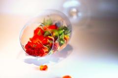 Glass vas som fylls med röda roskronblad aromatherapy begrepp Royaltyfria Bilder
