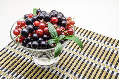 Glass vase with black and red currant on bamboo. Napkin stock images
