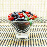 Glass vase with black and red currant. On a napkin stock photography