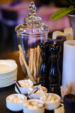 Glass vase with bread snack and decorative candles on the table. Bread sticks in a glass vase, pepperbox, plates, saucers with sugar on a wooden table with stock image
