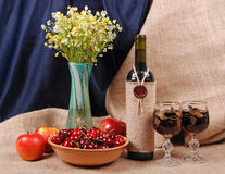 Glass vase with camomiles, apples and wine Stock Images