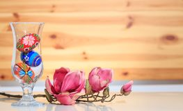 Glass vase with traditional painted Easter eggs and pearl necklace and a magnolia brach. Wooden wall. Glass vase with colorful eggs and pearl nacklace and a Stock Photos