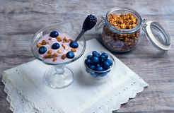 glass vase decorated with berries and granola yogurt Stock Image