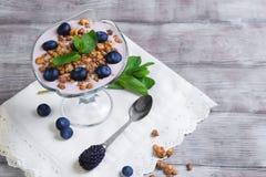 Glass vase decorated with berries and granola yogurt Stock Image