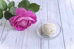 A marshmallow in a glass vase next to a rose. In a glass vase delicious marshmallow, next to a rose. The view from the top royalty free stock image