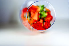 Glass vase filled with red rose petals. Aromatherapy concept. Royalty Free Stock Images