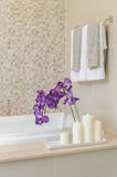 Glass vase of flower on bath tub with towel hanging Royalty Free Stock Photo