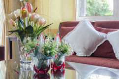 Glass vase of flower on glass table with red wooden sofa Stock Image