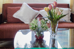 Glass vase of flower on glass table with wooden sofa Royalty Free Stock Photo