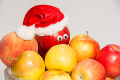 Glass vase of fruits with christmas boxes and hat. Big vase of fruits with decoration for christmas holiday. red santa clause hat is on the apple that has Royalty Free Stock Images