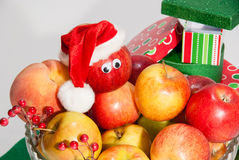 Glass vase of fruits with christmas boxes and hat. Big vase of fruits with decoration for christmas holiday. red santa clause hat is on the apple that has Royalty Free Stock Photos