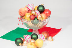 Glass vase of fruits christmas tree balls. Big vase of fruits: apples, peaches and pears with decoration for christmas holiday. The balls are different color Royalty Free Stock Photography