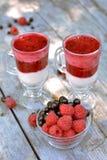 Glass vase full of fragrant red raspberry and blackberry near tasty yogurt with blended berries on grey table. Glass vase full of fragrant red raspberry and Stock Images