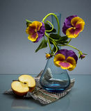 Glass vase with pansy and apple on black Stock Photography