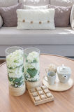 Glass vase of plants and tea cup set on wooden round table Royalty Free Stock Images
