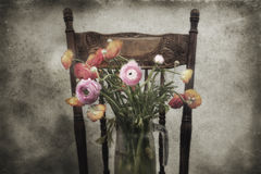 Glass vase of flowers on chair Stock Images