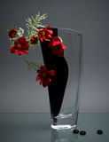 Glass vase with red flowers on gray Royalty Free Stock Photos
