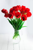 Glass vase with red tulips on wood table Royalty Free Stock Photo