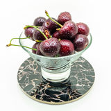 Glass vase on a stand with fresh wet cherries on white background. Glass vase on a stand with fresh wet cherries isolated on white background stock photos