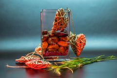 Glass vase with stones grass and harts stock image