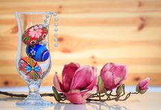 Glass vase with traditional painted Easter eggs and pearl necklace and a magnolia brach. Wooden wall. Glass vase with colorful eggs and pearl nacklace and a Royalty Free Stock Photography