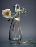 Glass vase with white flower and chaplet on gray Royalty Free Stock Image