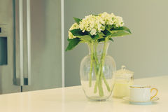 Glass vase of white flowers and teacup in a kitchen with blurred. Glass vase of white flowers, teacup and candle in a kitchen with blurred fridge behind in soft royalty free stock image
