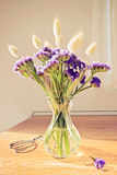 Glass vase with wild blue flowers on a wooden table Royalty Free Stock Image