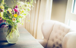 Glass vase with  wild field flowers bunch on dinning table with chair at window. Royalty Free Stock Photo