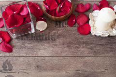 Glass vase and wood bow filled with red and white rose petals, white aromatic vanilla candle. Wooden background. Stock Images