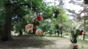 Glass vases with flowers hanging from tree. Glass vases  flowers hanging tree stock video footage