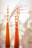 Glass vases with flowers. Glass orange vases, containing dry flowers Stock Photo