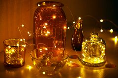 Glass vases, jars and candlesticks with led lights on a wire. Cozy details of home decor