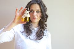 A glass of vegetal oil. A glass bottle with vegetal oil in the hand of a young lady stock photography