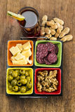 Glass of vermouth with cheese, olives , salami, nuts and peanuts. On a wood table Stock Photo